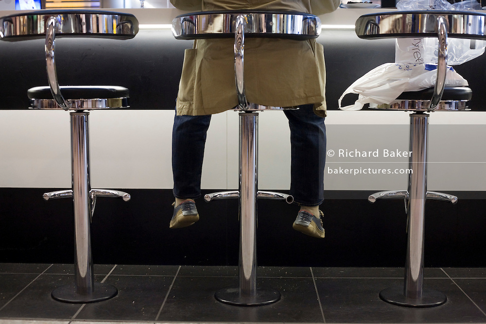 Male customer's legs dangling at Luxury caviar and assorted seafood displayed at Caviar House & Prunier at Heathrow T5
