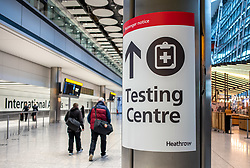 © Licensed to London News Pictures. 15/02/2021. London, UK. Passengers walk past a Testing Centre sign at London Heathrow Terminal 5 this morning as hotels near Heathrow start to accept quarantine passengers. From today, (Monday 15 February 2021) anyone arriving from a red-list destination must quarantine at a designated hotel and pay a hotel fee of £1,750 for a 10 day quarantine period. Photo credit: Alex Lentati/LNP