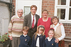 Extended family standing together outside house; with three generations,