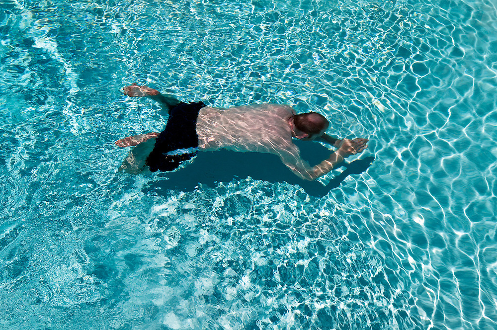 Ein mittelalter Mann in einem Swimmingpool   middle aged man in a swimming pool, cement pool    