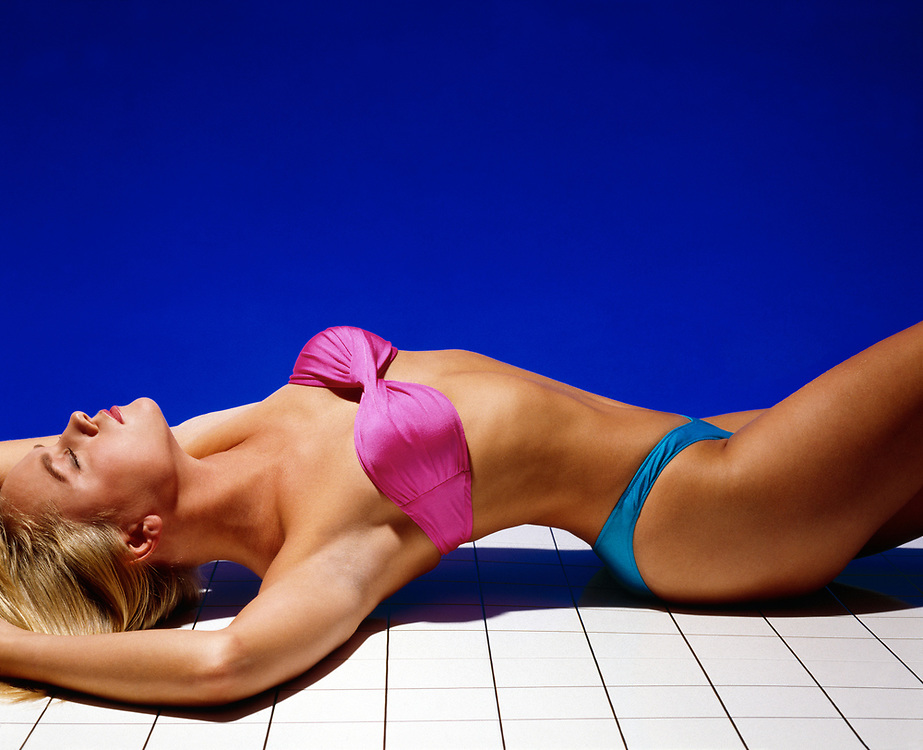 Blond haired woman in pink and turquoise bikini laying on white tile platform with a blue background