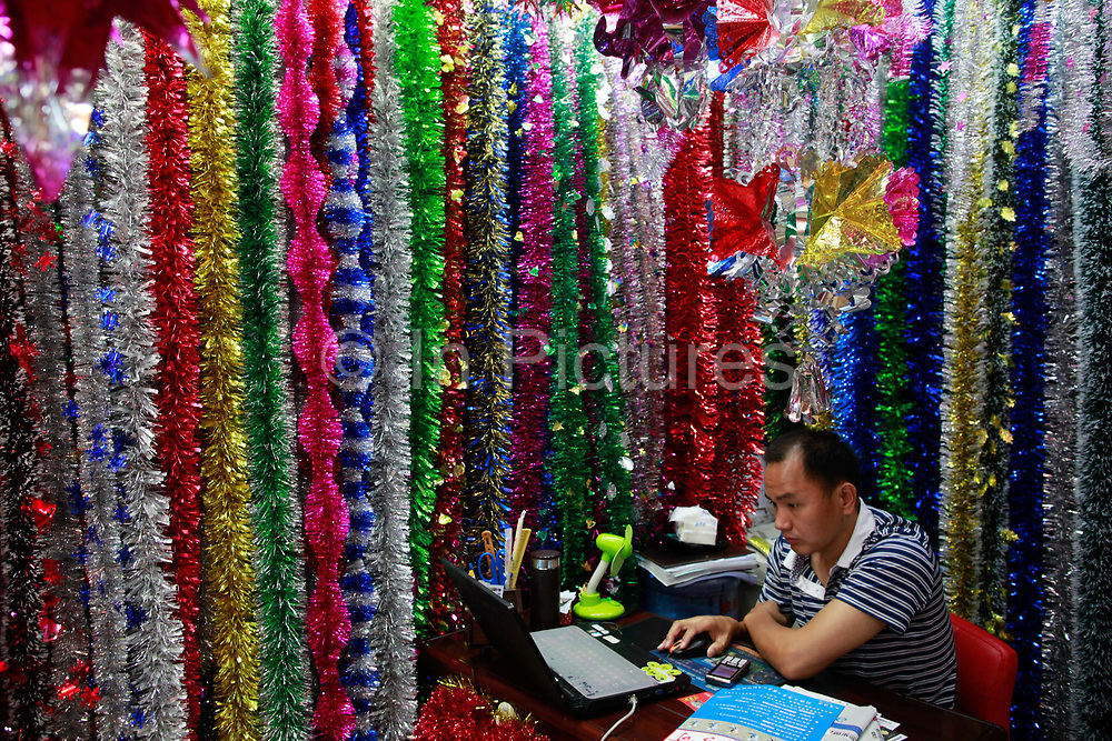 A man sits in his stall selling Christmas trees ornaments at the Yiwu International Trade City in Yiwu, Zhejiang Province, China on Sunday, 11 September 2011.  As the trading hub for small and medium manufacturers and exporters in the Yangtze River Delta region, Yiwu faces an uncertain future as export orders decline due to the slow economic recoveries of China's two largest trading partners, Europe and the United States