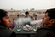15-year olds smoke water pipes (hookahs) in a tea shop overlooking Imam Square, Isfahan, Iran. (From the book What I Eat: Around the World in 80 Diets.)  In the distance, a view of the magnificently tiled Masjed-e Imam (Royal Mosque)  built by the Safavid ruler, Shah Abbas 1, as part of the renovation of the central square of Isfahan.