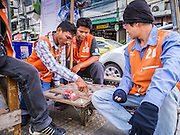 """04 APRIL 2013 - BANGKOK, THAILAND: Motorcycle taxi drivers play checkers while they wait for customers at a taxi stand in Bangkok. Thailand's economic expansion since the 1970 has dramatically reduced both the amount of poverty and the severity of poverty in Thailand. At the same time, the gap between the very rich in Thailand and the very poor has grown so that income disparity is greater now than it was in 1970. Thailand scores .42 on the """"Ginni Index"""" which measures income disparity on a scale of 0 (perfect income equality) to 1 (absolute inequality in which one person owns everything). Sweden has the best Ginni score (.23), Thailand's score is slightly better than the US score of .45.   PHOTO BY JACK KURTZ"""