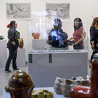 Visitors browse the artwork displayed at the Ingham Chapman Gallery during a fundraising art sale for the Art Student Collective at the University of New Mexico Gallup Tuesday.
