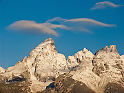 Lenticular clouds (lens shaped standing-wave clouds) hover in winds blowing over the peaks of Grand Teton and Teewinot, in Grand Teton National Park, Wyoming, USA. The 40 mile (64 km) long Teton Range is the youngest mountain chain in the Rocky Mountains, and began their uplift 9 million years ago, during the Miocene Epoch.
