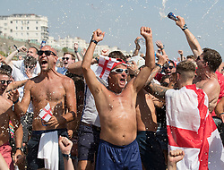 i© Licensed to London News Pictures. 07/07/2018. Brighton, UK. Football fans on the beach in Brighton celebrate England's first goal as they watch a giant TV screen showing England's quarter-final against Sweden from the Russian World Cup. Photo credit: Peter Macdiarmid/LNP