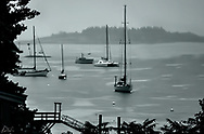 Image of a small harbor in Rockport, Maine on a very foggy day, rendered in Black & White.