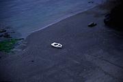 AJ02MF Small white dinghy boat alone on dark beach Lizard Point Cornwall England