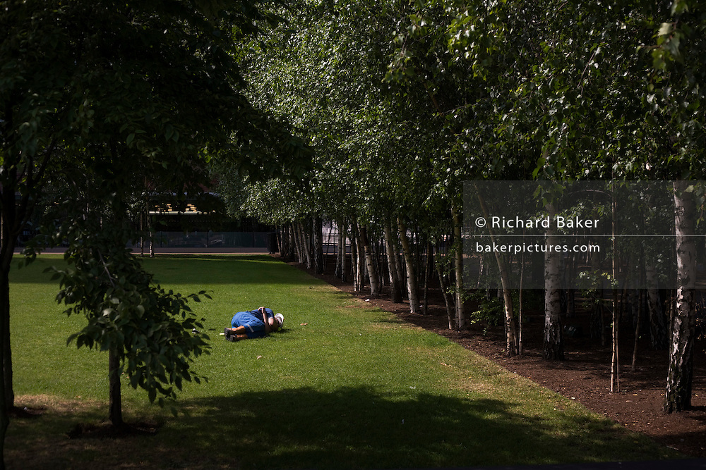 A construction worker still wearing his hard hat, takes a quick nap on the grass outside Tate Modern.