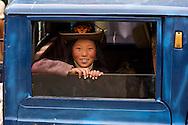 A Tibetan cowgirl peeks from behind a pickup truk's window in Litang, Tibet.