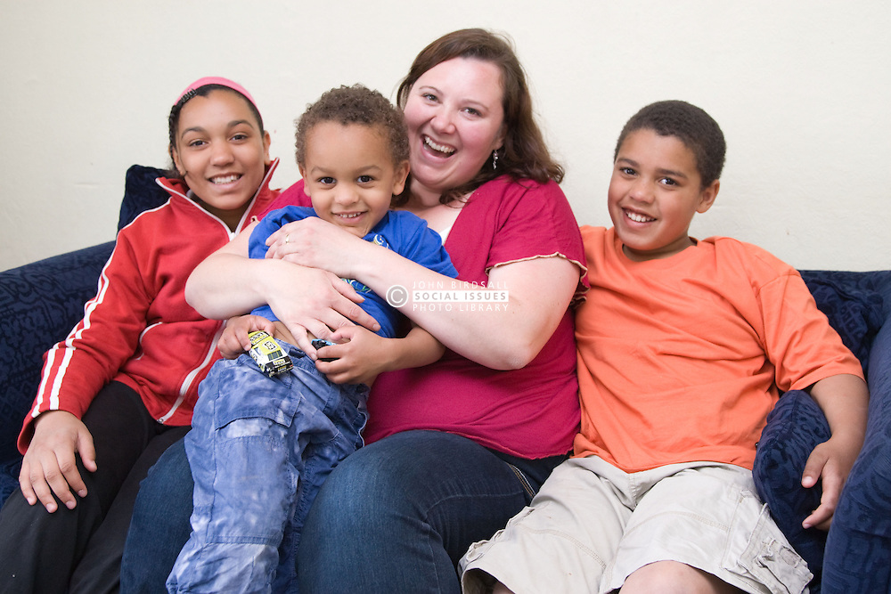 Single mum and her happy young family sitting on the sofa together at home,