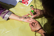 Guests receive Henna tattoos during the Pomeroy Multicultural Festival at Pomeroy Elementary School in Milpitas, California, on April 25, 2015. (Stan Olszewski/SOSKIphoto)
