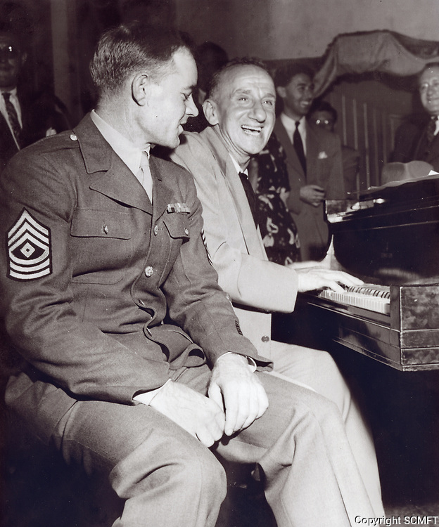 1943 Jimmy Durante sings while Sgt. Carl Bell sits on the piano bench. Sgt. Bell was the millionth serviceman to visit the Hollywood Canteen