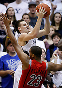 BYU guard Kyle Collinsworth, top, is fouled by Arizona forward Derrick Williams (23) as he attempts to score during the second half of an NCAA college basketball game, Saturday Dec. 11, 2010 in Salt Lake City. BYU defeated Arizona 87-65. (AP Photo/Colin E Braley)