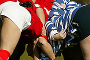 Benfica and Tecnico teams struggle in a scrum action during a match.
