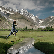 A boy jumps over a stream in a mountain landscape.