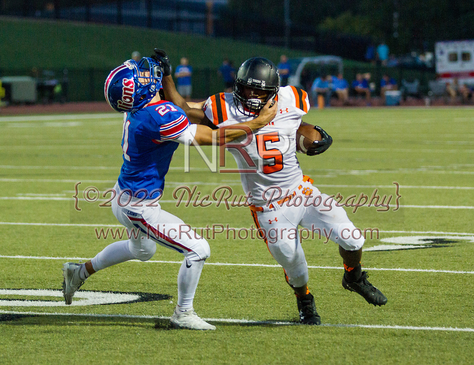 Traevon Edmundson (#5) gives a good stiff arm to the Lions, Colton Albert (#21) as he runs for a Tigers first down.