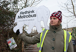 © Licensed to London News Pictures.  002/02/2015. Bristol, UK.  Nic holds a placard as campaigners against the Bristol Metrobus junction which is planned to replace the allotments by the M32 have occupied some trees due to be cut down.  Some campaigners are sitting in nets and platforms in the trees but expect an attempt will be made to evict them.  Security contracters are putting up fencing. The land is exceptionally fertile and has traditionally been used for market gardens and allotments, but part has been designated for a bus junction off the motorway to help improve transport in Bristol.  Bristol is this year's European Green Capital.  Photo credit : Simon Chapman/LNP