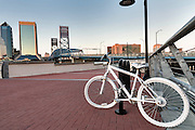 A ghost bike memorial to cyclists killed in accidents along the Southbank Riverwalk along the St. John's River at sunset in Jacksonville, Florida.