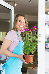 Portrait of mid adult woman holding potted plant of flower, smiling