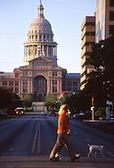Couple with dog crossing the street in front of the capitol building in Austin, TX