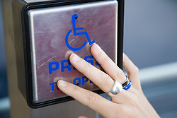 Woman's hand on a disability access door button,