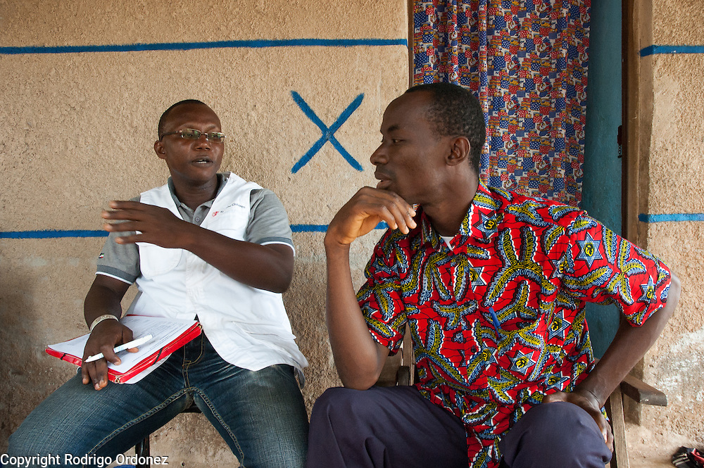 A Save the Children staff member (left) talks to Maimouna's father Toumari, 38, at the family's home in Duékoué, western Côte d'Ivoire.<br /> Maimouna had been separated from her family for three months, since the moment armed conflict broke out in her hometown, Duékoué, and she had to flee to Man. Save the Children facilitated the reunion with her parents and her return home.