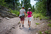 Mother and daughter holding holding hands while hiking in Glacier National Park