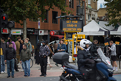 © Licensed to London News Pictures. 23/10/2021. London, UK. Members of the public walk past Covid-19 sign in east London as Health Secretary Sajid Javid warned Covid 19 cases could reach 100,000 a day this winter and urged people to take precautions against the virus. Photo credit: Marcin Nowak/LNP