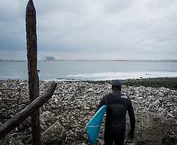 © Licensed to London News Pictures. 18/01/2014<br /> <br /> Teesside, England<br /> <br /> A surfers on the North east coast of England walks towards the waters edge as he goes for a surf.<br /> <br /> Photo credit : Ian Forsyth/LNP
