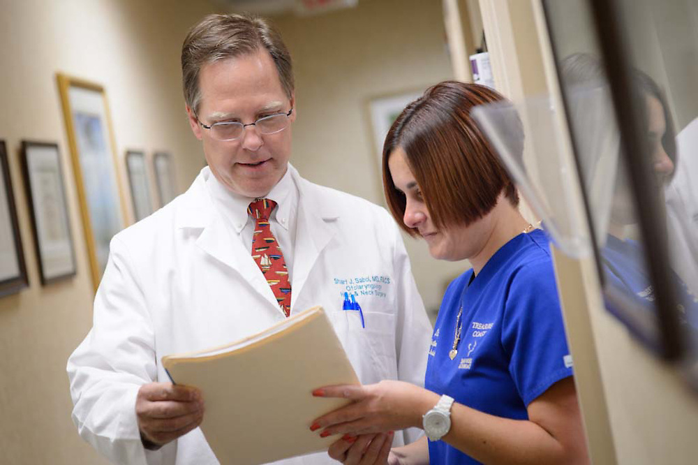 Image of a Doctor consulting with a medical assistant looking over a chart in a private office setting.