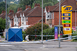 CAPTION UPDATE © Licensed to London News Pictures. 31/07/2021. High Wycombe, UK. A large police tent and a forensic investigator next to a Jet petrol station on Micklefield Road as a murder investigation is launched in High Wycombe following the discovery by a police patrol of a person on the ground at approximately 12:20BST surrounded by a group of males who fled the scene when the police officers arrived, despite the efforts of police and paramedics the man died at the scene. Photo credit: Peter Manning/LNP