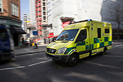 Ambulance rushes by with lights blazing on way to an emergency. London, UK.