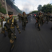 Soldiers march towards a burning barricade in the capital Tegucigalpa