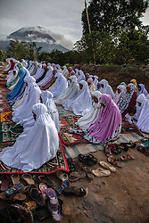 June 15, 2018 - Karo, North Sumatra, Indonesia - Indonesian Muslims offer Eid al-Fitr prayers to mark the end of the holy fasting month of Ramadan as Mount Sinabung seen in the background at Karo, North Sumatra. Millions in Indonesia, the world's most populous Muslim country, are celebrating Eid with family reunions and feasts of traditional food after a month of prayer and fasting. (Credit Image: © Ivan Damanik via ZUMA Wire)