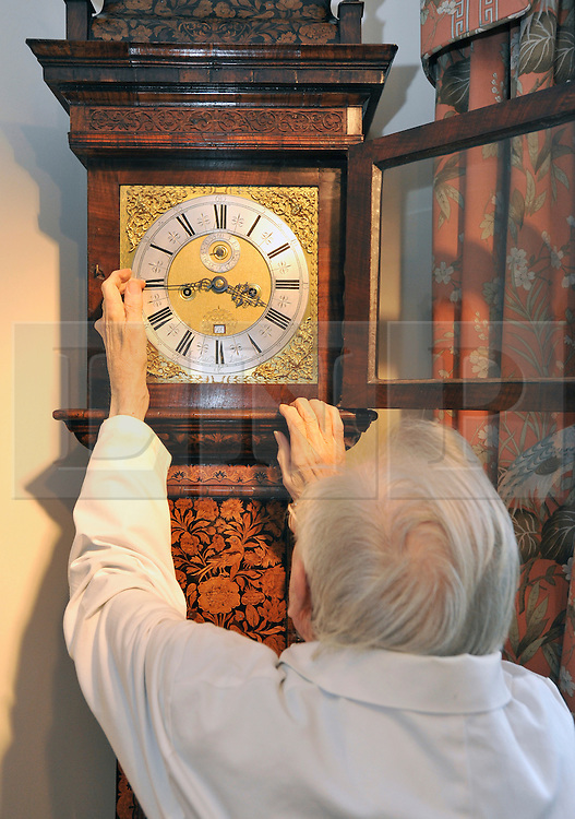 """©London News pictures...28/10/2010.  Dudley Taylor (76) a clock maker all his life, changes the time on a Marquetre clock dated cira 1700. Staff at Horological Workshops start the task of changing the 100's of clocks at their store in Guildford, Surrey, UK. Micahel Tooke who has owned the store for 43 years and worked in the clock business all his life said. """"at this time of year we get alot of people who bring clocks in for repair after they have changed the time incorreectly by winding back the hands manually"""""""