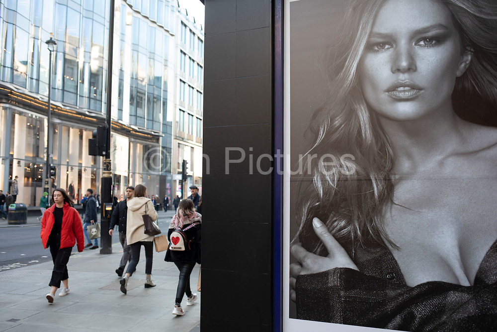 Advertising poster of an alluring model interacts with passing shoppers on Oxford Street on 21st January 2020 in London, England, United Kingdom. Aspirational pictures of models are used widely in society to lure people into desiring the goods they are advertising using beautiful models. Oxford Street is a major road in the West End of London. It is Europes busiest shopping street, with around half a million daily visitors, and has approximately 300 shops.