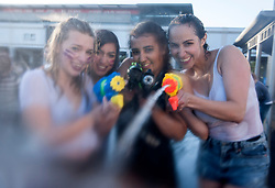 "© Licensed to London News Pictures. 03/06/2015. Bristol, UK.  Left-right: Ala Roszkiewicz age 15, Hanna Coss age 15, Camille Vaz age 16 from Brazil, Angelita Vaz age 35 from Brazil. Giant water fight in Bristol's Millennium Square, organised by The Smile Instigation Collective, a group who say they are dedicated to ""infecting people with happy"".   It is to celebrate the last session of the Smile Instigation Collective and includes decorating the fountains at Millennium Square with recycled flowers.  Photo credit : Simon Chapman/LNP"
