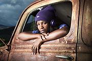 Portrait en couleur d'une jeune femme calédonienne dans une vielle voiture pour le calendrier de la ville de Païta.