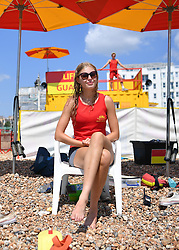 © Licensed to London News Pictures. 22/07/2021. Brighton, UK. Lifeguard Anna surveys the beach with colleague Thomas (background) on a busy afternoon. As COVID restrictions relax and the UK continues to open up, Brighton experiences an influx of visitors making the most of the summer heat. Meanwhile transmission of the virus continues to double every 9 days. Photo credit: Guilhem Baker/LNP