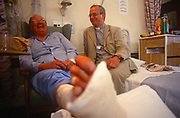 An Anglican vicar shares a joke with a patient whose leg is in plaster, in a ward of the London Hospital, Whitechapel, on 23rd June 1993, in London, England.