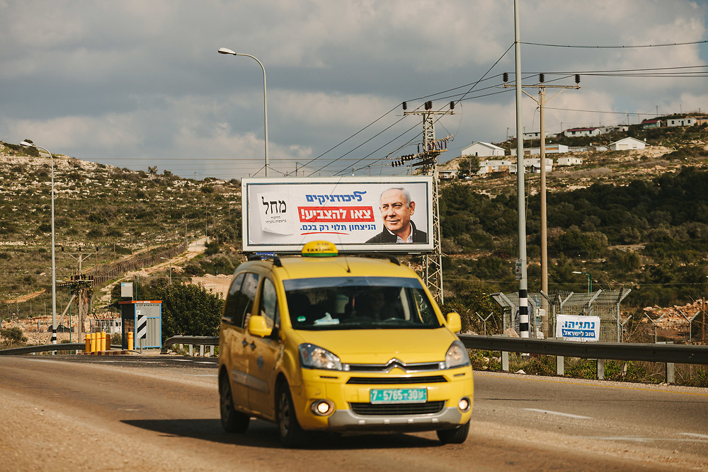 A Palestinian taxi drives past an election billboard for Israeli Prime Minister Benjamin Netanyahu and the Likud party, near  the West Bank Jewish settlement of Karnei Shomron, on February 21, 2020.