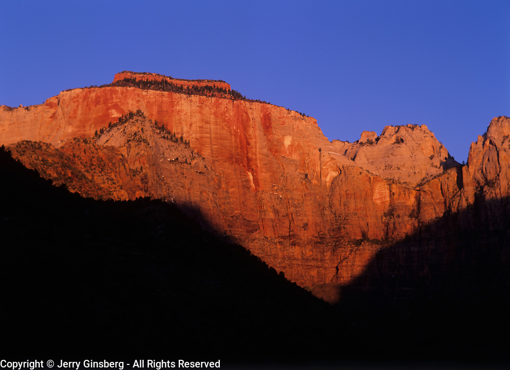 The first rays of sunrise strike enormous West Temple in Zion Canyon, Zion National Park, Utah.