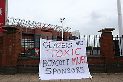 © Licensed to London News Pictures. 13/05/2021. Manchester, UK. A sign is left outside Old Trafford by fans unhappy with the club's ownership. Thousands of fans gathered at the ground ahead of the rearranged match against Liverpool to protest against the ownership of the club by the Glazer family.  Photo credit: Adam Vaughan/LNP