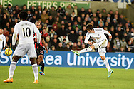 Ki Sung-Yueng of Swansea city ®  has a shot at goal. Barclays Premier league match, Swansea city v Queens Park Rangers at the Liberty stadium in Swansea, South Wales on Tuesday 2nd December 2014<br /> pic by Andrew Orchard, Andrew Orchard sports photography.
