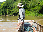Boatman So's son Sonmvang (18) takes a rest after pushing the boat up rapids on the Nam Ou river during the dry season when the river level is low, Phongsaly province, Lao PDR. The Nam Ou river connects small riverside villages and provides the rural population with food for fishing. But this river and others like it, that are the lifeline of rural communities and local economies are being blocked, diverted and decimated by dams. The Lao government hopes to transform the country into 'the battery of Southeast Asia' by exporting the power to Thailand and Vietnam.