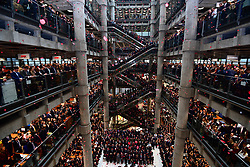 Poppies fall through the atrium of the Lloyd's building during the Lloyd's of London Armistice commemoration service.