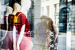 Couple in the city looking at clothing store window