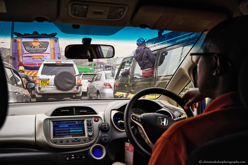 An Uber driver is stuck in a traffic jam between Matatus and cars in the Nairobis' Central Business District. In the Kenyan capital  the classic taxis are also more and more replaced by the cheaper internet service Uber. But the Matatus are still the cheapest means of transport in Kenya. If the traffic jams the journey with the Uber can become very expensive and offers not even a speed advantage compared to the Matatus. The fare to the Matatus, on the other hand, is only slightly higher during the rush hours.